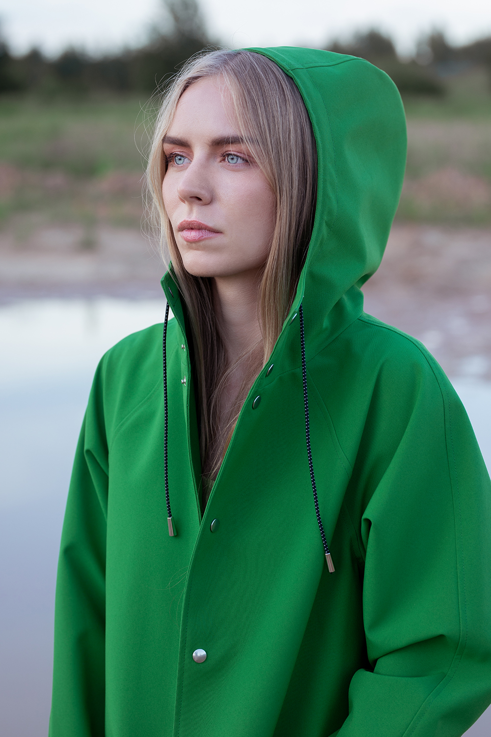 A woman's wearing a waterproof, windproof and breathable unisex raincoat in the nature